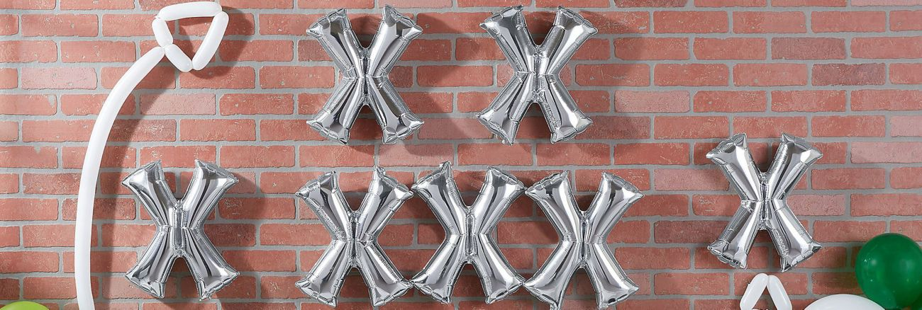 Silver foil balloons on a brick wall