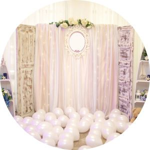 Pink backdrop with a mirror and flowers in the center. Pink latex balloons air filled on the floor.